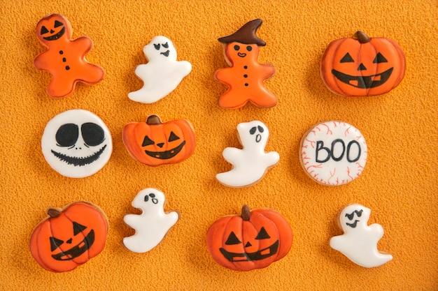 おいしいハロウィーンのクッキー、カボチャと幽霊。オレンジ色の背景にハロウィーンのジンジャーブレッドクッキー。自家製クッキー。