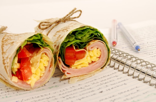 Delicious ham wrap on the notebook