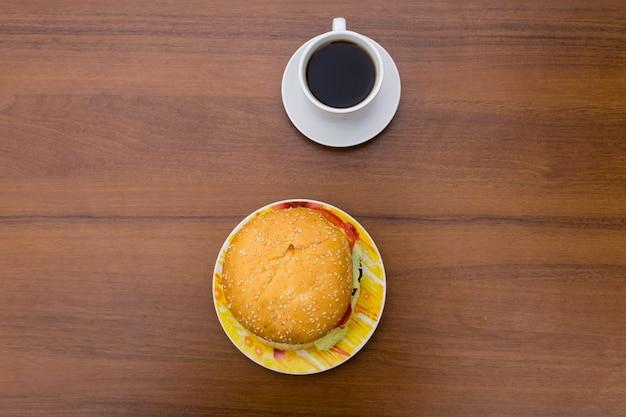 木製のテーブルの上においしいハンバーガーとコーヒーのカップ。上面図