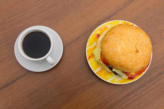 Delicious hamburger and cup of coffee on wooden table. top view