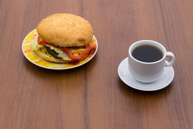 Delicious hamburger and cup of coffee on wooden table