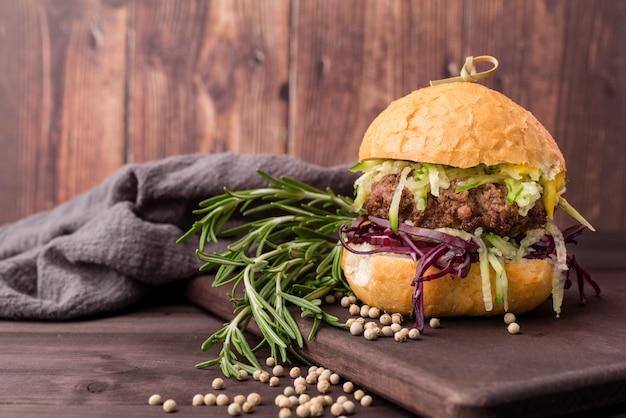 Вкусный гамбургер перед деревянной стеной