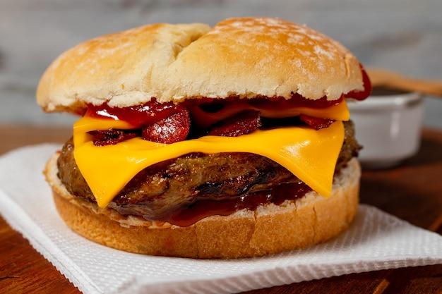 木製の表面と素朴な背景に種とケチャップを添えた自家製パンにベーコンとチェダーチーズを添えたおいしいハンバーガー。