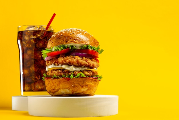 Delicious hamburger with cola on a yellow background