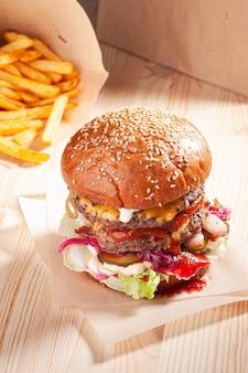 木製のテーブルにフライドポテトとおいしいハンバーガー