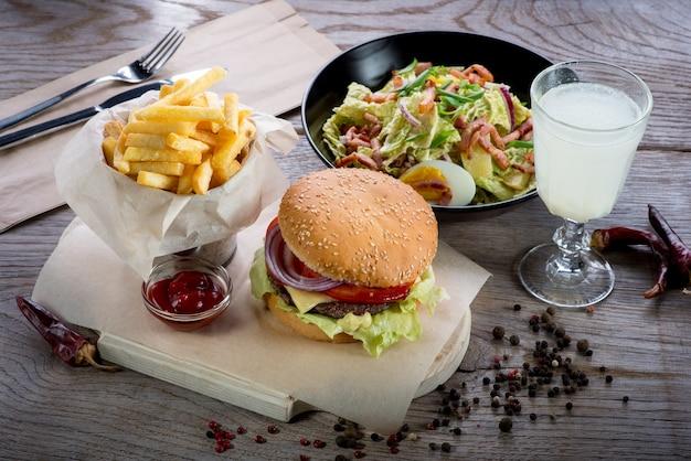 Вкусный гамбургер с картофелем фри и салатом на деревянном столе