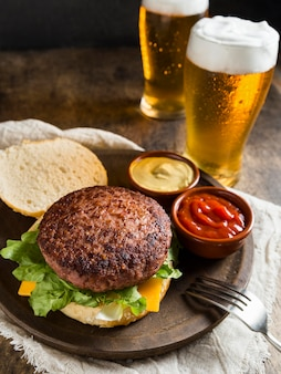 Delicious hamburger with glasses of beer and sauce