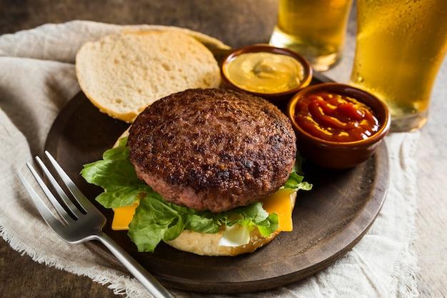 Вкусный гамбургер с бокалами пива и кетчупом