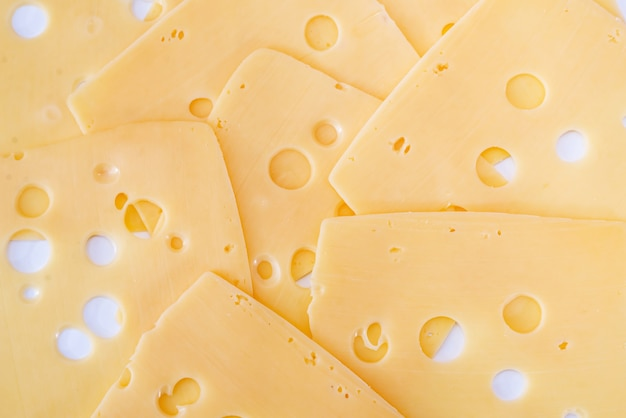 Delicious hard cheese with holes as a background.