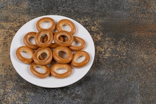 Вкусные твердые крекеры на белой тарелке.