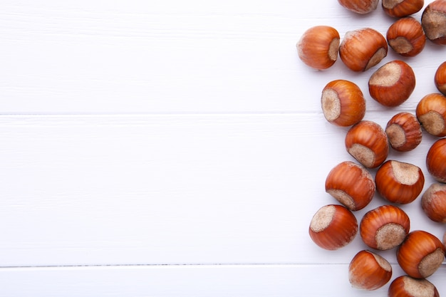 Delicious hazelnut on a white wooden background