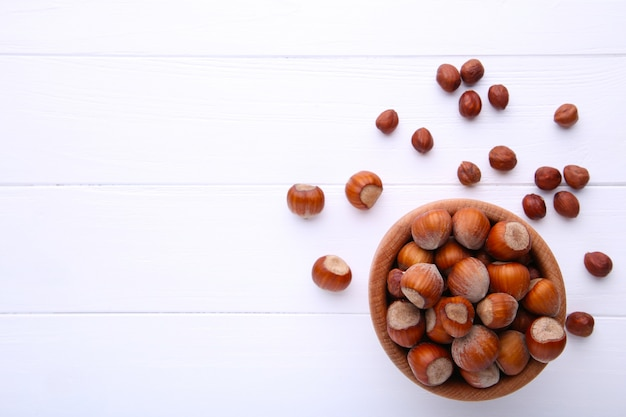 Delicious hazelnut in the wooden bowl on white