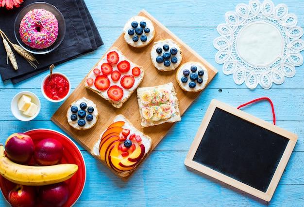 おいしい健康的な朝食、別の詰め物、チーズ、バナナ、イチゴ、釣り、バター、ブルーベリー、別の木製の背景のフルーツサンドイッチ。