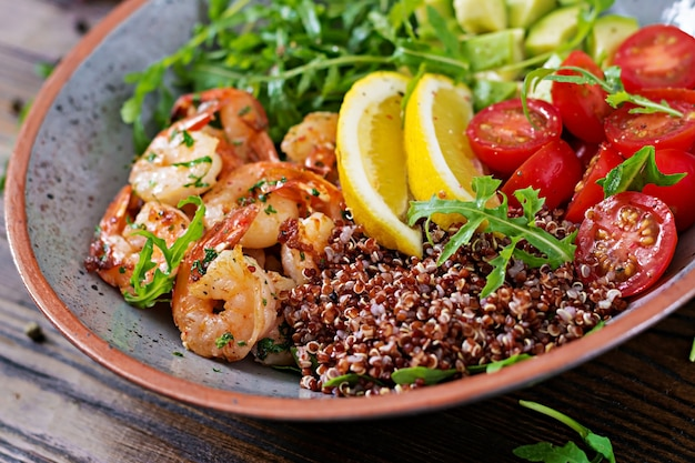 Delicious healthy buddha bowl with shrimps, tomato, avocado, quinoa, lemon and arugula on the wooden table. healthy food.