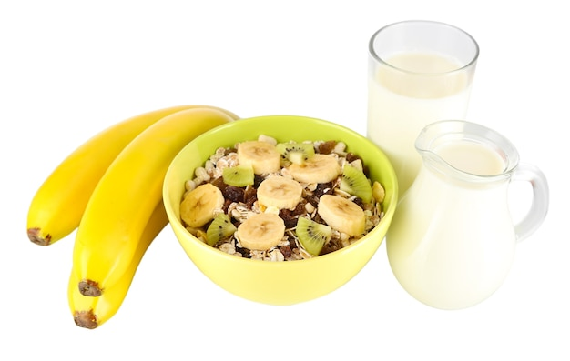 Delicious and healthy cereal in bowl with milk and fruit on white