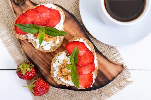 Вкусный полезный диетический завтрак: ржаной хлеб с творогом и клубникой и чашка кофе