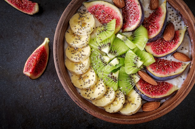 Delicious and healthy oatmeal with figs, kiwi, banana, almond and chia seeds.
