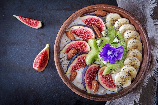 Delicious and healthy oatmeal with figs, kiwi, banana, almond and chia seeds