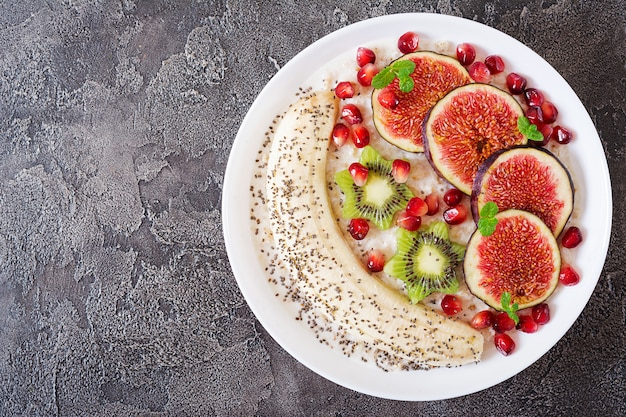 Delicious and healthy oatmeal with figs, kiwi, pomegranate, banana and chia seeds.