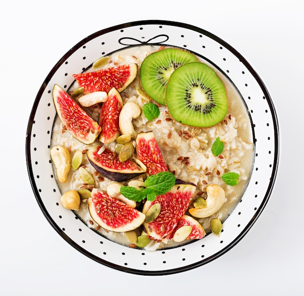 Delicious and healthy oatmeal with figs, nuts, kiwi and seeds isolated