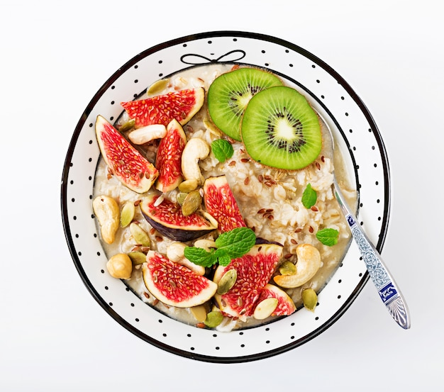 Delicious and healthy oatmeal with figs, nuts, kiwi and seeds