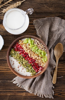 Delicious and healthy oatmeal with kiwi, pomegranate and seeds. healthy breakfast. fitness food. proper nutrition. rustic style. flat lay. top view