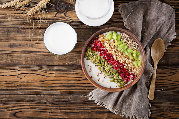 Delicious and healthy oatmeal with kiwi, pomegranate and seeds. healthy breakfast. fitness food. proper nutrition. rustic style. flat lay.