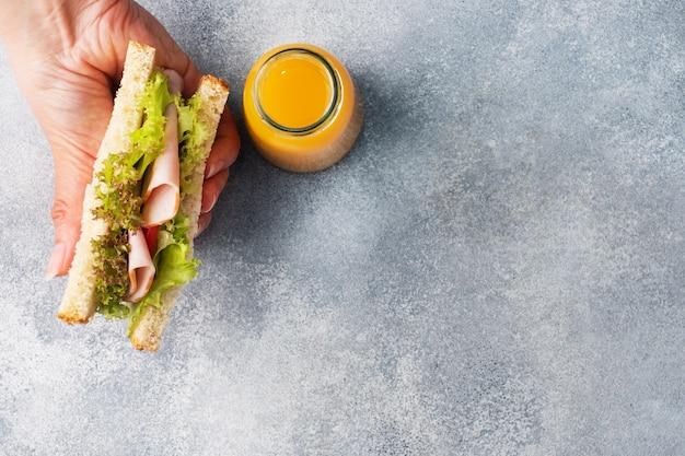 女性の手で軽食の朝食のためのおいしい健康的なサンドイッチ。トーストパントマトハムリーフサラダ、ボトル入りジュース、コピースペース