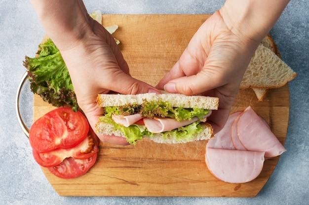 女性の手で軽食の朝食のためのおいしい健康的なサンドイッチ。トーストパントマトハムリーフサラダ。