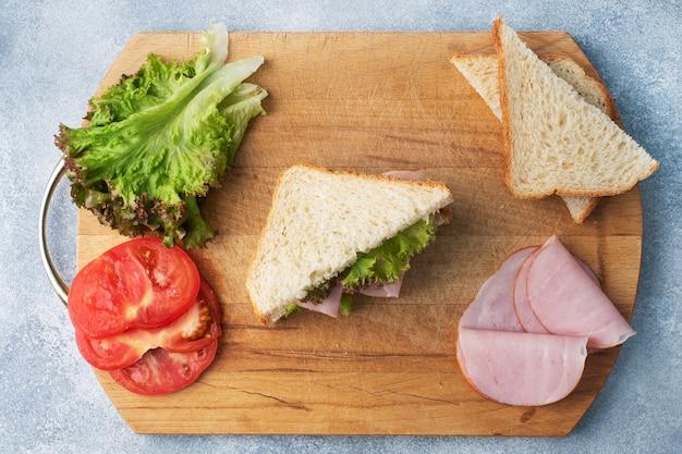 木製のまな板、上面図で軽食の朝食のためのおいしい健康的なサンドイッチ。トーストパントマトハムリーフサラダ。