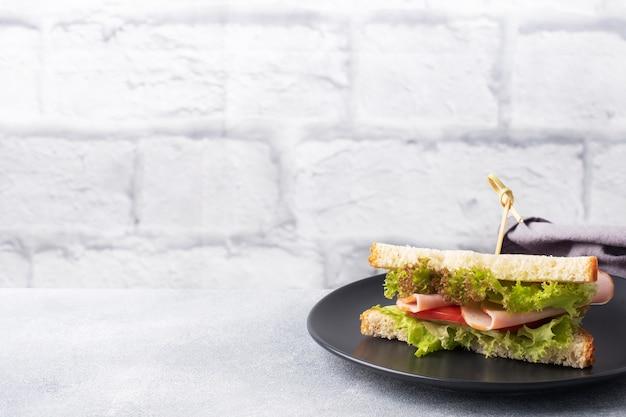 軽食の朝食のためのおいしい健康的なサンドイッチ。トーストパントマトハムリーフサラダ。コピースペース