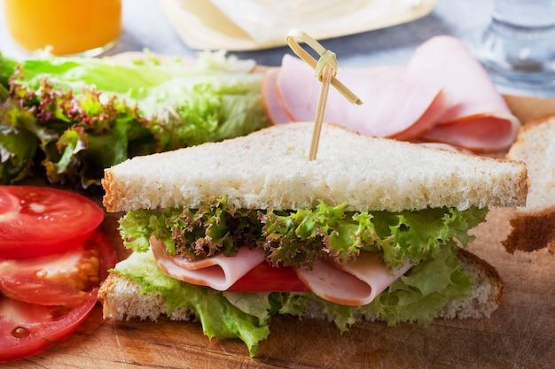 軽食の朝食のためのおいしい健康的なサンドイッチ。トーストパントマトハムリーフサラダ。