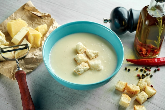 Delicious and hearty cream cheese soup with croutons in a blue bowl on a wooden table. restaurant food