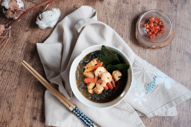 Delicious herb black noodles with broth and shrimp in the ceramic bowl