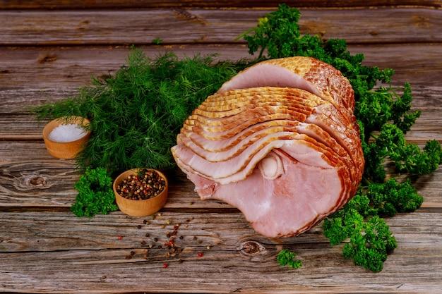 Вкусный праздничный обед, нарезанный медовый свиной окорок.
