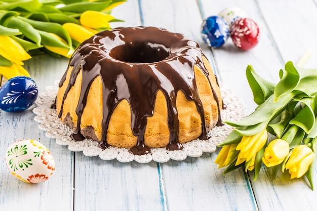 Вкусный праздничный словацко-чешский торт бабовка с шоколадной глазурью. пасхальные украшения - весенние тюльпаны и яйца.