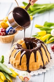Вкусный праздничный словацко-чешский торт бабовка с шоколадной глазурью. заливка шоколадного топпинга. пасхальные украшения - весенние тюльпаны и яйца.