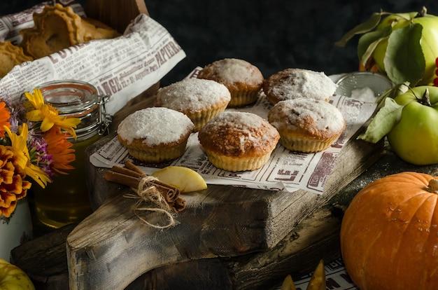 暗い表面に粉砂糖をまぶしたおいしい自家製リンゴとカボチャのマフィン、ハロウィーンの秋の焼き菓子
