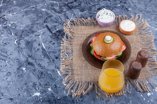 大理石のテーブルの上においしい自家製ハンバーガーとフレッシュジュースのグラス。