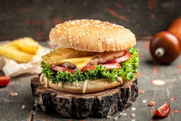 Вкусный домашний бургер из говядины, сыра и овощей. жирная нездоровая пища. место для текста