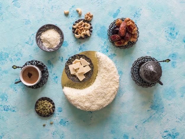 Вкусный домашний торт в форме полумесяца, подается с финиками и кофейной чашкой.