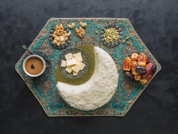 Вкусный домашний торт в форме полумесяца, подается с финиками и кофейной чашкой