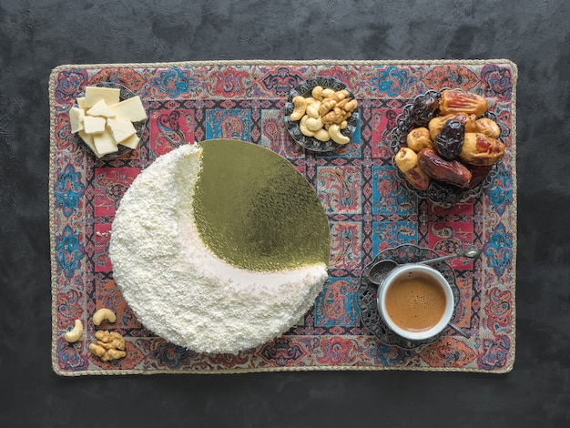 Delicious homemade cake in the shape of a crescent moon, served with dates and coffee cup
