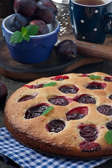 Delicious homemade cake with plums on a wooden background