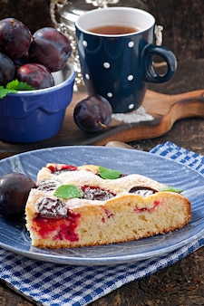 Delicious homemade cake with plums on a wooden surface