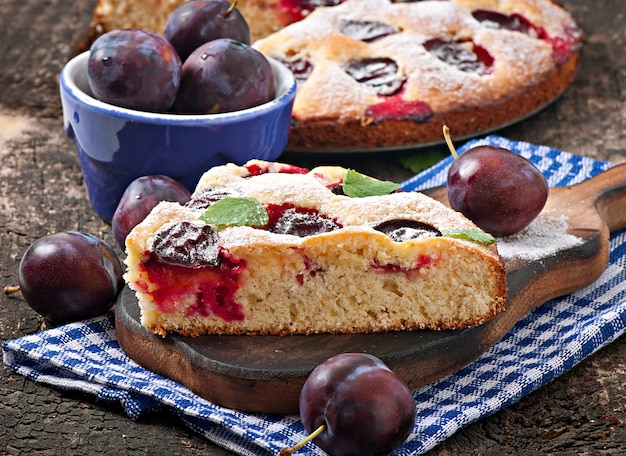 Delicious homemade cake with plums on a wooden table