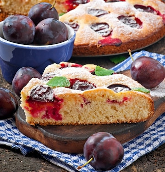 Delicious homemade cake with plums on a wooden