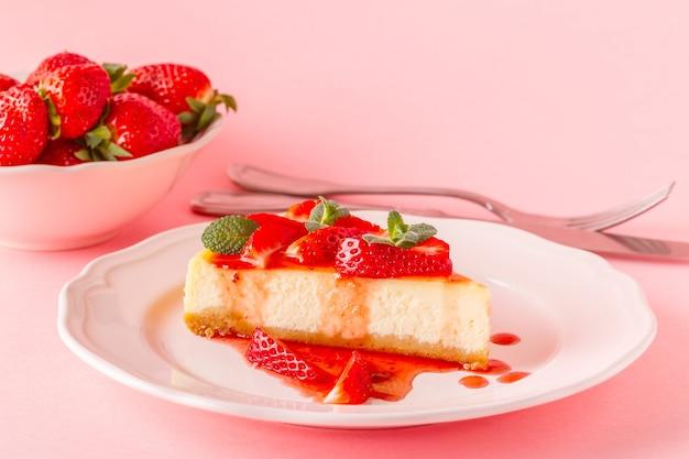 ピンクの背景にイチゴとおいしい自家製チーズケーキ。