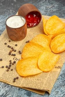 회색 테이블에 신문에 맛있는 수제 칩과 후추 그릇 마요네즈 케첩