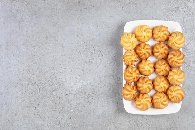 大理石の背景のプレートにおいしい自家製クッキーが並んでいます。高品質の写真